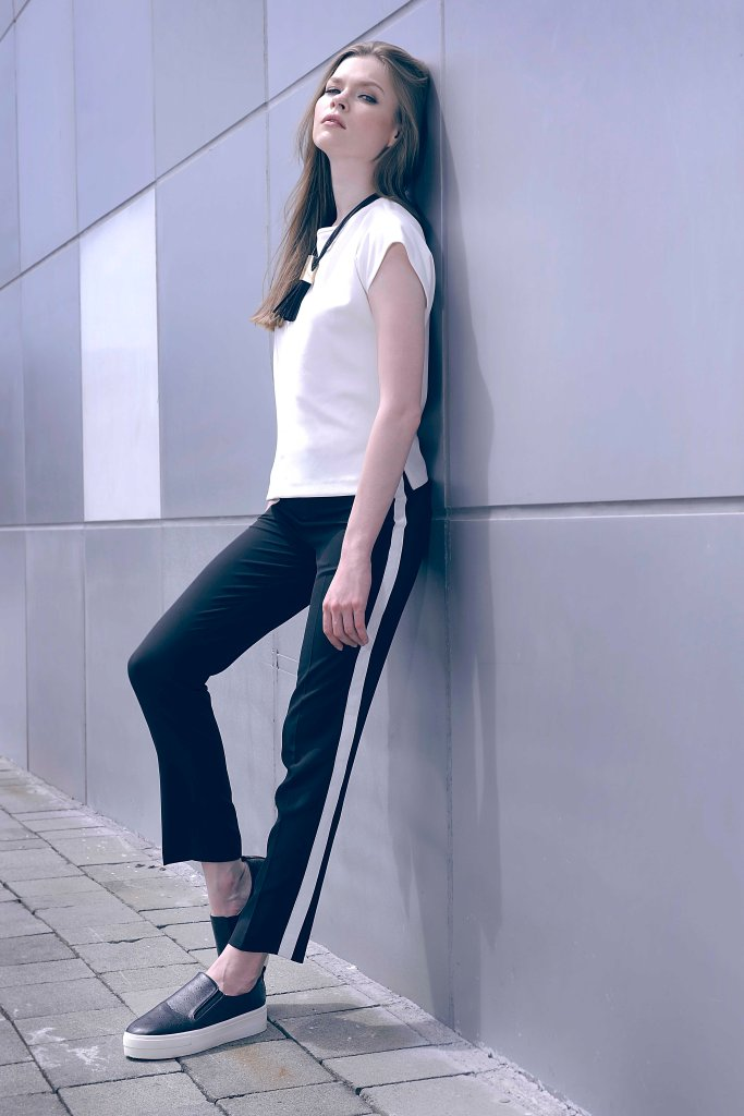 Minimalist match. White boxy top worn with black trousers with contrasting side piping.